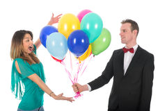Young man giving balloons to girl friend Stock Image