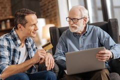 Young man giving bank card to his father using laptop. Online banking. Handsome young men giving a bank card to his elderly father using a laptop and starting royalty free stock images