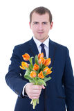 Young man giving bunch of tulips  isolated on white Royalty Free Stock Photo