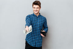 Young man giving cash to camera. Young handsome man giving cash fron wallet to camera royalty free stock photos