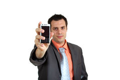 Young man giving cellphone. A young businessman, holding a cellphone, pointing it in front of him Royalty Free Stock Photography