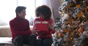 Man giving christmas present to girlfriend at home. Young man giving christmas gift to his beloved girlfriend at home stock video footage