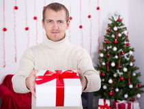 Young man giving christmas present box over christmas background Royalty Free Stock Photography