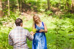 Young man giving a flower dandelion to girlfriend outdoors Royalty Free Stock Photography
