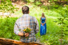 Young man giving a flower dandelion to girlfriend outdoors Stock Photos