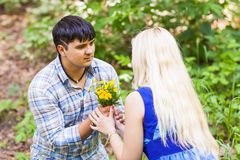 Young man giving a flower dandelion to girlfriend outdoors Stock Photography
