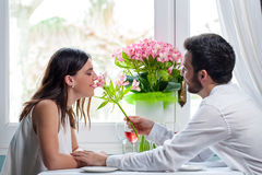 Young man giving flower to girlfriend in restaurant. Royalty Free Stock Photography