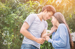 Young man giving a flower to his girlfriend. Romantic moment: young men giving a flower to his girlfriend stock photography