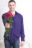 Young man giving flowers Stock Photography