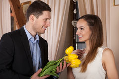 Young man giving flowers Stock Images