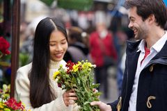 Young man giving flowers to beautiful woman Royalty Free Stock Photos