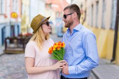 Young man giving flowers to his girlfriend. Young men giving flowers to his girlfriend or wife Stock Image