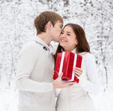 Young man giving a gift to his girlfriend for Christmas Stock Image