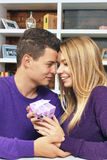 Young man giving a gift to his girlfriend Stock Images