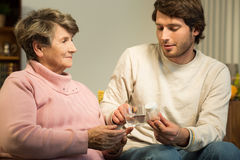 Young man giving grandmother medicament Royalty Free Stock Photo
