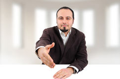 Young man giving hand for handshake. Young smiling man giving his hand for a handshake in his office Stock Photos