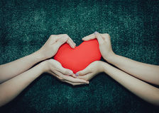 Young man giving a heart-shaped pillow his sweetheart on Valentine`s Day. Love beautiful concept. Stock Images