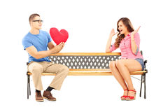 Young man giving a heart to a surprised female Royalty Free Stock Image
