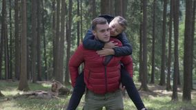Young man giving his girlfriend a piggy back ride having fun in their hike in the forest -. Young man giving his girlfriend a piggy back ride having fun in their stock footage