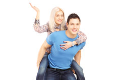 Young man giving his girlfriend a piggy back ride. Young men giving his girlfriend a piggy back ride, isolated against white background royalty free stock photos