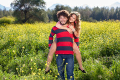 Young man giving his girlfriend a piggy back. Smiling young men giving his girlfriend a piggy back as they enjoy a relaxing day together in the countryside royalty free stock photo