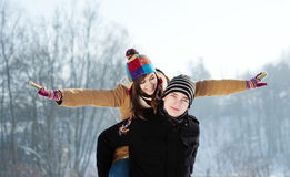 Young man giving his girlfriend a piggyback ride. Winter collection: young couple in winter Royalty Free Stock Photo