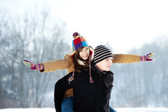 Young man giving his girlfriend a piggyback ride. Winter collection: young couple in winter Royalty Free Stock Images