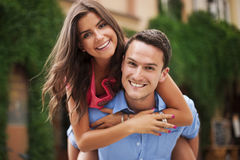 Young man giving his girlfriend a piggyback ride Royalty Free Stock Photo
