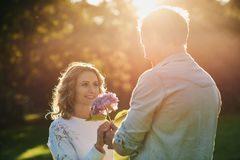 Young man giving his smiling wife flowers at sunset. Handsome young men giving his beautiful wife a bouquet of purple wild flowers while enjoying a romantic Stock Photography