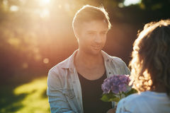 Young man giving his wife a bouquet of wild flowers. Handsome young men giving his wife a bouquet of purple wild flowers while enjoying a romantic afternoon in a Stock Photos