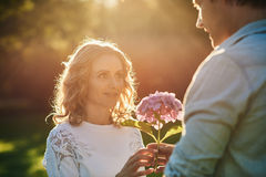 Young man giving his wife flowers under the afternoon sun. Handsome young men giving his beautiful wife a bouquet of purple wild flowers while enjoying a Royalty Free Stock Photo