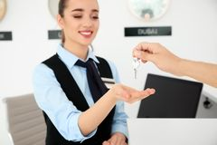 Young man giving key to receptionist. In hotel royalty free stock photography