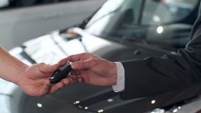 Young man giving keys of car to buyer. Men shaking hands in beautiful car dealership on background of bought cars. Young man giving keys of car to buyer. Men stock footage