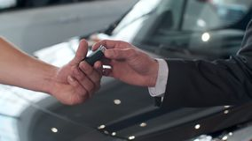 Young man giving keys of car to buyer. Men shaking hands in beautiful car dealership on background of bought cars. Young man giving keys of car to buyer. Men stock video footage