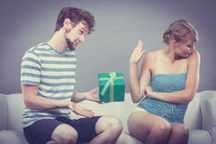 Young man giving offended woman gift box Royalty Free Stock Images