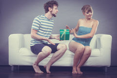 Young man giving offended woman gift box Royalty Free Stock Photography