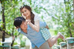 Young man giving a piggy back to his girlfriend royalty free stock photo