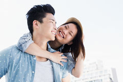 Young man giving a piggyback ride to woman Royalty Free Stock Photography