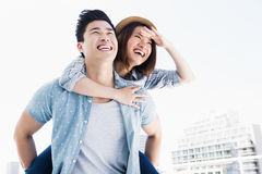 Young man giving a piggyback ride to woman Royalty Free Stock Photos