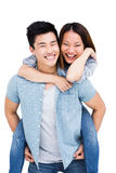 Young man giving piggyback ride to woman Royalty Free Stock Images