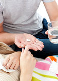 Young man giving pills to his morbid girlfriend. Close-up of young man giving pills to his morbid girlfriend in the living room Stock Photography
