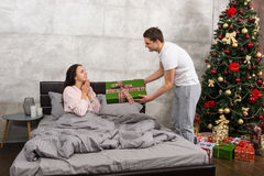 Young man giving a present to his happy girlfriend, while she si. Young men giving a present to his happy girlfriend, while she sitting on a bed and wearing Royalty Free Stock Image