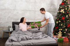 Young man giving a present to his surprised girlfriend, while sh. Young men giving a present to his surprised girlfriend, while she sitting in a bed and wearing Stock Photo