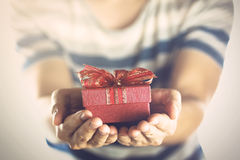 Young man giving and presenting a gift to someone. Young man giving and presenting a gift to someone Stock Photo