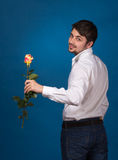 Young man giving a red rose. On blue background Stock Photography