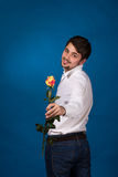 Young man giving a red rose. On blue background Royalty Free Stock Photography