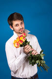 Young man giving a red rose. On blue background Royalty Free Stock Photo