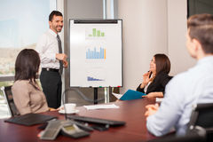 Young man giving a sales pitch. Attractive young men giving a sales pitch to a group of clients in a meeting room Stock Photography