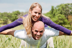 Young man giving shoulder ride to her girlfriend Stock Photography