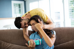 Young man giving a surprise gift to woman in the living room Royalty Free Stock Photo